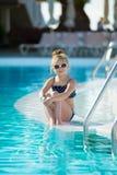Niña adorable con las gafas de sol por la piscina Foto de archivo