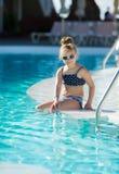 Niña adorable con las gafas de sol por la piscina Imágenes de archivo libres de regalías