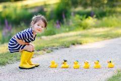 Niña adorable con los patos de goma en parque del verano Foto de archivo