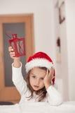Niña adorable con una linterna de la Navidad a disposición, esperando f Imagen de archivo
