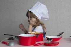 Niña adorable del retrato en comida del cocinero del sombrero del cocinero El bebé se sienta en la tabla en la cocina y piensa Imagen de archivo libre de regalías