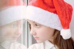 Niña adorable en el sombrero de Papá Noel cerca de la ventana Imagen de archivo