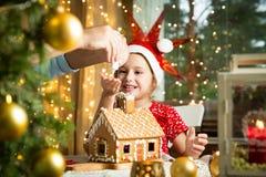 Niña adorable en sombrero rojo que adorna la casa de pan de jengibre de la Navidad con el esmalte Foto de archivo libre de regalías