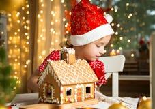 Niña adorable en sombrero rojo que adorna la casa de pan de jengibre de la Navidad con el esmalte Imagen de archivo