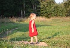 Niña adorable en vestido rojo brillante Fotos de archivo