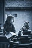 Niña adorable, escribiendo la letra a Papá Noel, sentándose en un viento Imágenes de archivo libres de regalías