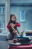 Niña adorable, escribiendo la letra a Papá Noel, sentándose en un viento Foto de archivo