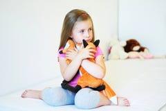 Niña adorable que abraza el juguete de la felpa del zorro en cama Fotos de archivo