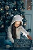 Niña adorable que abre un regalo mágico de la Navidad por un árbol de navidad Imagen de archivo libre de regalías