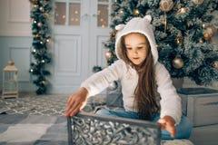 Niña adorable que abre un regalo mágico de la Navidad por un árbol de navidad Foto de archivo