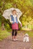 Niña adorable que camina con el perro en lluvia Fotos de archivo libres de regalías
