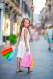 Niña adorable que camina con los panieres al aire libre en Roma Forme al niño del niño en ciudad italiana con sus compras Fotografía de archivo libre de regalías