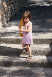 Niña adorable que camina y que sostiene una barra de pan Fotos de archivo