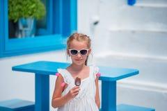 Niña adorable que come el helado al aire libre en el verano en la ciudad Foto de archivo