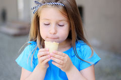 Niña adorable que come el helado sabroso en el parque en día de verano soleado caliente Foto de archivo libre de regalías