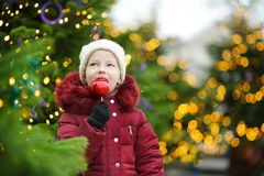 Niña adorable que come la manzana roja cubierta con la formación de hielo del azúcar en mercado tradicional de la Navidad Imagenes de archivo