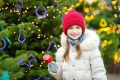 Niña adorable que come la manzana roja cubierta con la formación de hielo del azúcar en mercado tradicional de la Navidad Imagen de archivo libre de regalías