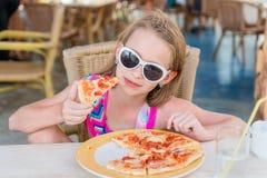Niña adorable que come la pizza para el almuerzo Foto de archivo libre de regalías