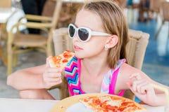 Niña adorable que come la pizza para el almuerzo en café al aire libre Imagenes de archivo