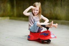 Niña adorable que conduce un coche del juguete Imágenes de archivo libres de regalías