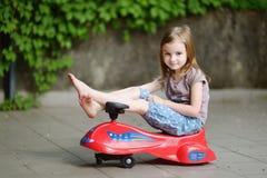 Niña adorable que conduce un coche del juguete Fotos de archivo