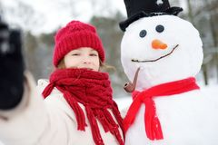 Niña adorable que construye un muñeco de nieve en parque hermoso del invierno Niño lindo que juega en una nieve imagen de archivo