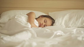 Niña adorable que duerme en una cama Carro tirado derecha a izquierda metrajes