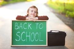 Niña adorable que espera un autobús escolar Imagenes de archivo