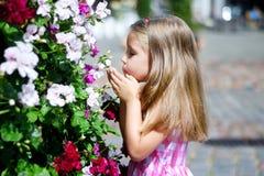 Niña adorable que juega cerca de arbusto de la flor en un parque de la ciudad Fotografía de archivo libre de regalías