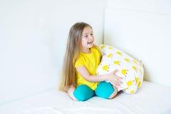 Niña adorable que juega con la almohada en la cama en su dormitorio Imágenes de archivo libres de regalías