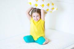 Niña adorable que juega con la almohada en la cama en su dormitorio Imagen de archivo