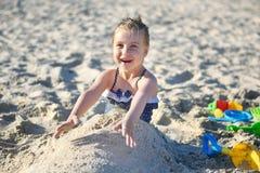 Niña adorable que juega con la arena en la playa en verano Imágenes de archivo libres de regalías