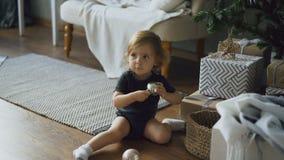 Niña adorable que juega con las bolas del juguete que se sientan cerca del árbol de navidad en casa Imagen de archivo libre de regalías