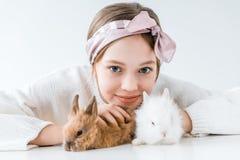 Niña adorable que juega con los conejos y que sonríe en la cámara Imagen de archivo libre de regalías