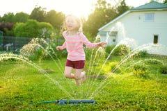 Niña adorable que juega con una regadera en un patio trasero en día de verano soleado Niño lindo que se divierte con agua al aire fotos de archivo libres de regalías
