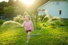 Niña adorable que juega con una regadera en un patio trasero en día de verano soleado Niño lindo que se divierte con agua al aire foto de archivo libre de regalías