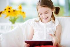 Niña adorable que juega con una tableta digital Imagen de archivo