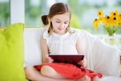 Niña adorable que juega con una tableta digital Foto de archivo libre de regalías