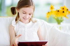 Niña adorable que juega con una tableta digital Imágenes de archivo libres de regalías