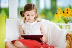 Niña adorable que juega con una tableta digital Imagenes de archivo