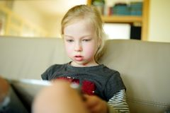 Niña adorable que juega con una tableta digital en casa Historietas y películas de observación de Childr fotos de archivo