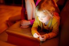 Niña adorable que juega con una tableta digital en un cuarto oscuro Niños que se divierten junto en casa fotografía de archivo