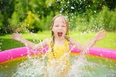 Niña adorable que juega en piscina inflable del bebé Niño feliz que salpica en centro colorido del juego del jardín en día de ver fotos de archivo