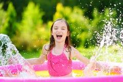 Niña adorable que juega en piscina inflable del bebé Niño feliz que salpica en centro colorido del juego del jardín en día de ver foto de archivo libre de regalías