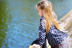 Niña adorable que juega por un río en parque soleado Fotos de archivo