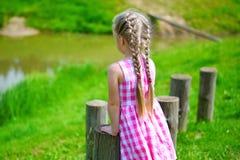 Niña adorable que juega por una charca en parque soleado en un día de verano hermoso Imagen de archivo libre de regalías