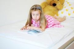 Niña adorable que miente en la cama y que lee un libro Fotos de archivo libres de regalías