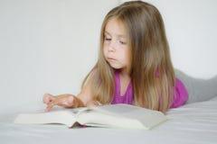 Niña adorable que miente en la cama y que lee un libro Fotografía de archivo libre de regalías