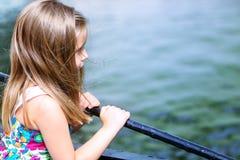 Niña adorable que mira el río en un día de verano hermoso Imagenes de archivo