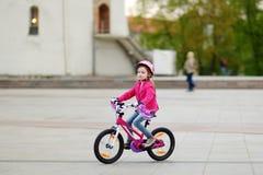 Niña adorable que monta una bici imágenes de archivo libres de regalías